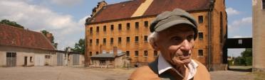 Ernesto Kroch vor dem Zellenbau (ehemaliges KZ Lichtenburg, Sachsen-Anhalt, Juni 2008). Hier war er von 1936/37 eingesperrt.